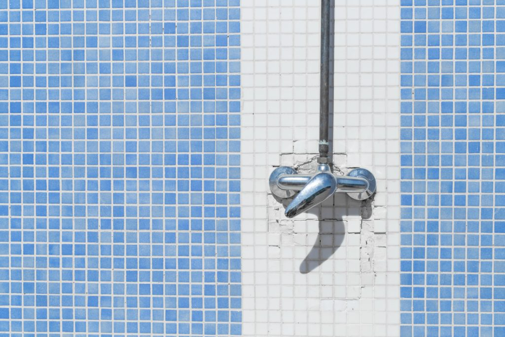 Shower faucet on white and blue mosaic tiles