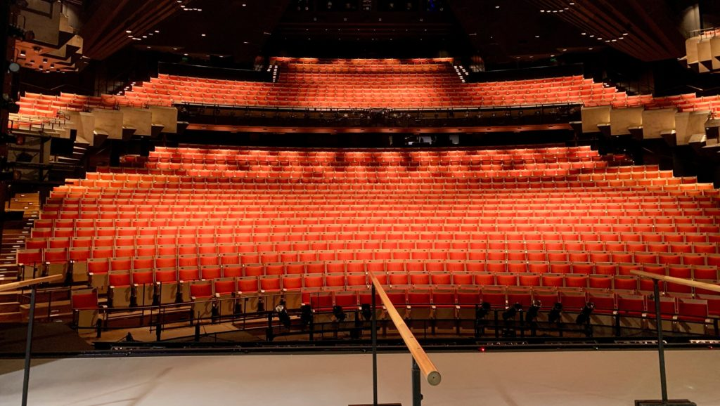 Become more confident when giving presentations: Stage of an opera house with red empty chairs in the audience