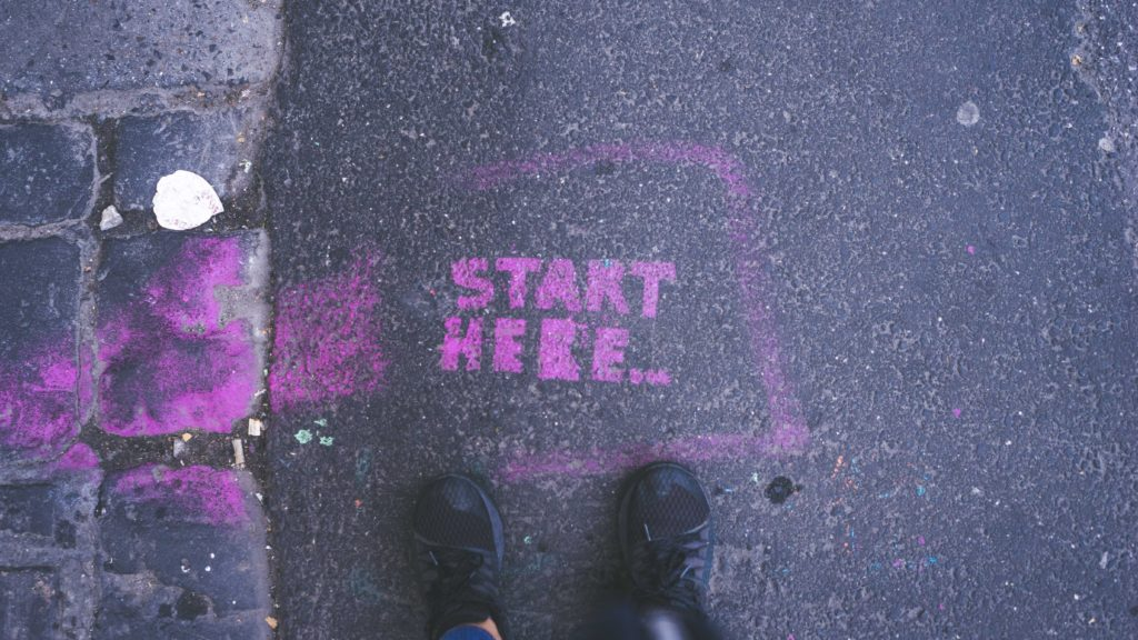 "Starting a PhD: Grafitti on asphalt reading ""Start here"" with shoes in front of it, perspective from top"