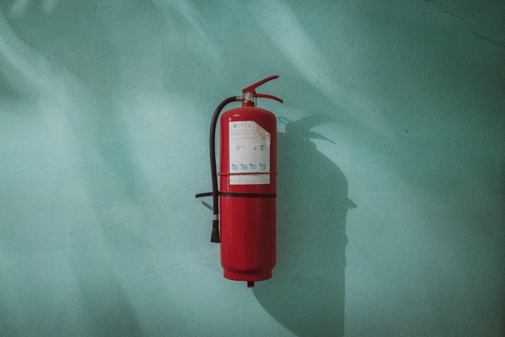 red fire extinguisher in front of blue wall