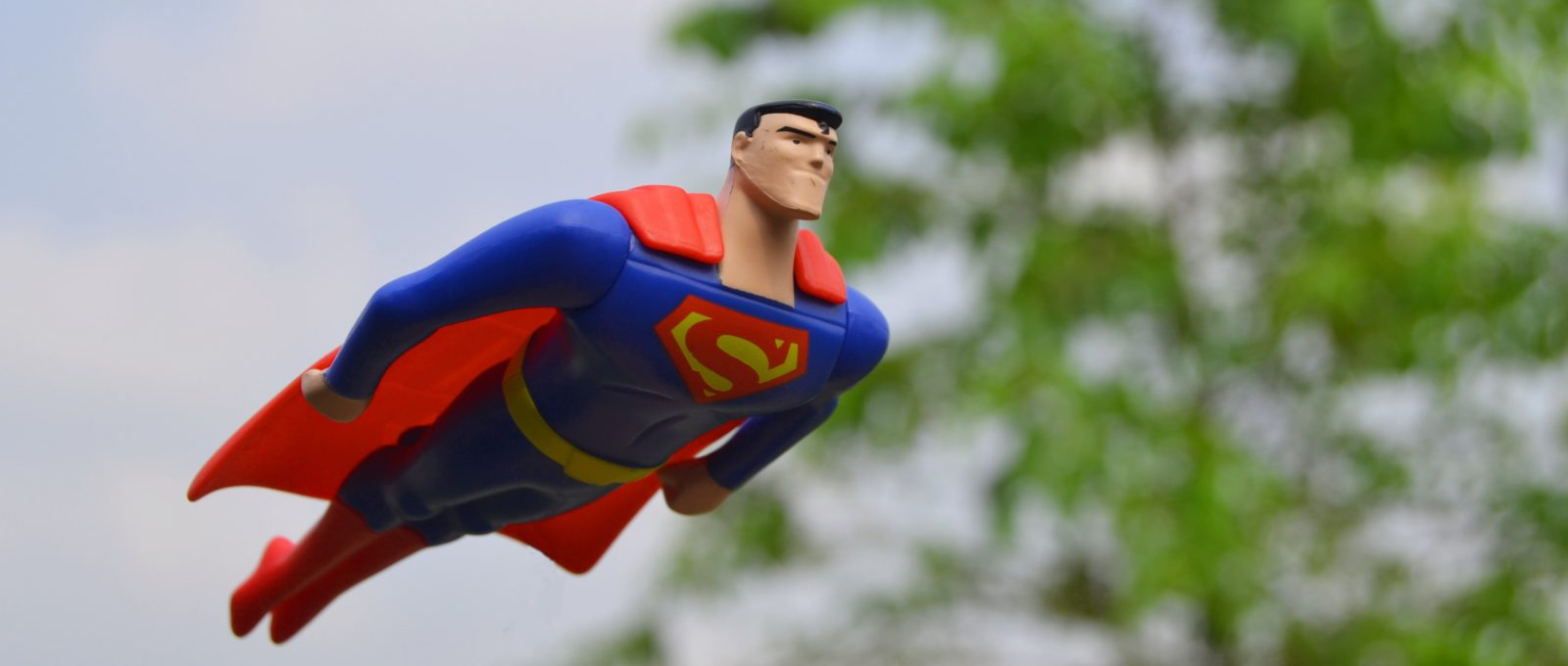 Superman Figure flying in front of green tree in blurry background