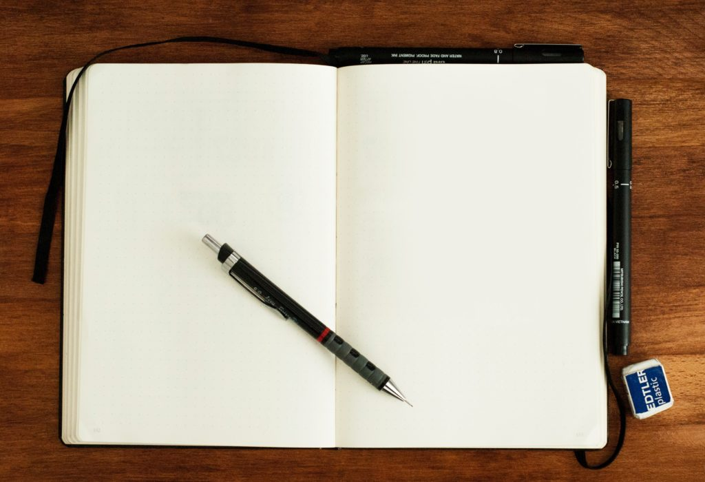 Empty notebook with blank pages, open, with pencil on top