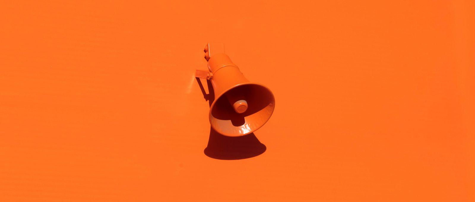 Orange microphone on orange background