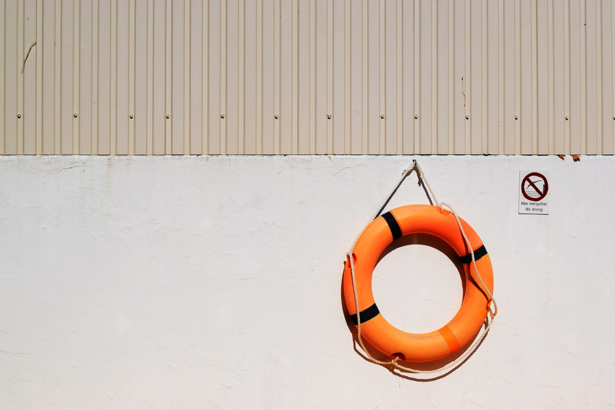 Orange Life Belt hanging from beige wall