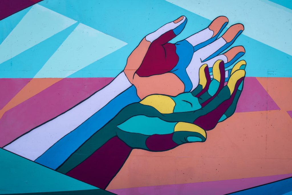 Grafitti of two hands reaching out for help