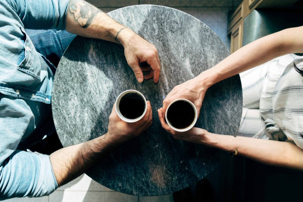Table from above with two friends drinking coffee who exchange PhD experiences