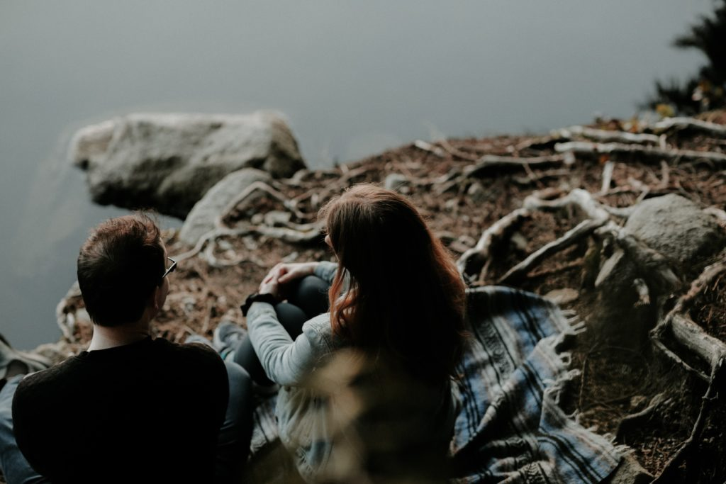 Two people sitting at a river bank talking